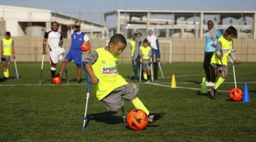 Seorang anak Palestina yang diamputasi menggiring bola saat berlatih di lapangan bermain al-Durra di kota Dier al-Balah, Jalur Gaza tengah (18/10/2019). Tim ini diawasi oleh pelatih Irlandia yang diamputasi Simon Baker.  (AP Photo/Hatem Moussa)