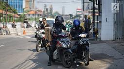 Pengendara motor berhenti saat melintas di Jalan KS Tubun, Petamburan, Jakarta Barat, Kamis (23/5/2019). Sisa gas air mata untuk membubarkan massa dalam kericuhan aksi 22 Mei masih terasa dan mengganggu aktvitas pengguna jalan, khususnya pengendara sepeda motor. (Liputan6.com/Immanuel Antonius)