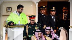 Raja Arab Saudi, Salman bin Abdulaziz Al Saud menuruni tangga eskalator saat tiba di Vnukovo International Airport, Rusia, 4 Oktober 2017. Eskalator emas itu mendadak macet dan membuat raja serta sejumlah pendampingnya  kebingungan (Alexander NEMENOV/AFP)