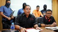 Agus berpakaian orange tersangka pembunuh Tardi saat diamankan di kantor Direktorat Reserse Kriminal Umum Polda Riau. (Liputan6.com/ M Syukur)