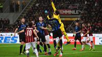 Aksi penyelamatan dilakukan Gianluiggi Donarumma pada laga lanjutan Serie A yang berlangsung di Stadion San Siro, Milan, Senin (18/3). Inter Milan menang 3-2 atas AC Milan. (AFP/Miguel Medina)