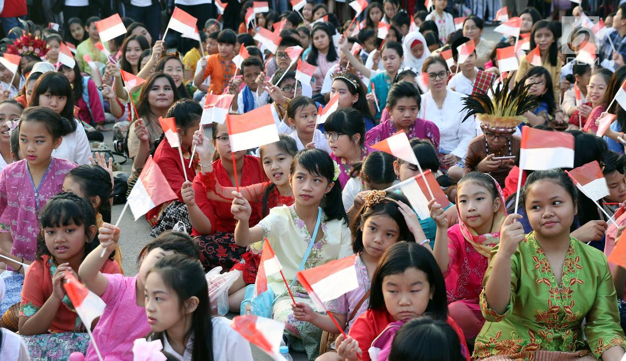 Ratusan anak-anak mengibarkan bendera Merah Putih saat gelaran Harmoni Indonesia 2018 di Kompleks Gelora Bung Karno, Jakarta, Minggu (5/8). Presiden RI, Joko Widodo hadir dalam acara tersebut. (Liputan6.com/Helmi Fithriansyah)