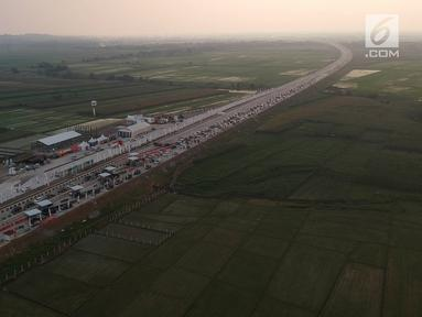 Foto udara antrean kendaraan pemudik di jalur tol fungsional Gerbang Tol (GT) Kertasari, Tegal, Jawa Tengah, Minggu (10/6). Memasuki H-5 lebaran GT Kertasari mulai dipadati kendaraan pemudik dari arah Jakarta. (Liputan6.com/Arya Manggala)