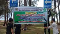 BKSDA Resor Agam memasang spanduk peringatan ada buaya muara di Pantai Tiku. (Liputan6.com/ BKSDA Agam)