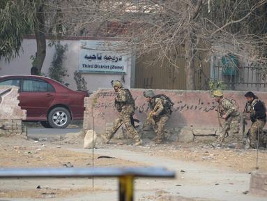 Tentara Afghanistan mengambil posisi di dekat sebuah kantor amal Inggris Save the Children saat terjadi serangan yang sedang berlangsung di Jalalabad, Afghanistan (24/1). (AFP Photo/Noorullah Shirzada)