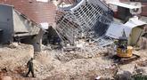 Petugas berada dekat rumah yang hancur tertimpa tanah longsor di Perumahan Nerada Estate Ciputat, Tangerang Selatan, Sabtu (12/6/2021). Tidak ada korban jiwa dalam peristiwa longsor yang menimpa sejumlah rumah akibat hujan deras yang terus menerus di kawasan tersebut. (Liputan6.com/Angga Yuniar)