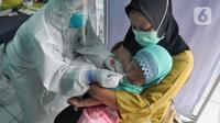 Paramedis melakukan swab test PCR kepada seorang anak di Puskesmas Kramat Jati, Jakarta Timur, Rabu (13/1/2020). Setiap harinya, Puskesmas Kramat Jati menyediakan kuota 300 swab test PCR  secara gratis untuk memutus mata rantai penyebaran COVID-19. (merdeka.com/Arie Basuki)
