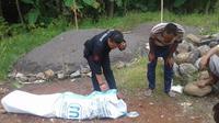 Petugas tengah melakukan pemeriksaan jenazah dalam karung di pantai Cibalong, pantai selatan, Garut (Liputan6.com/Jayadi Supriadin)