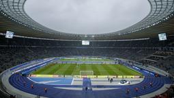 """Para pemain melakukan pemanasan di dekat Replika Tembok Berlin bertuliskan """"Bersatu menentang tembok.Bersatu untuk Berlin"""" berdiri jelang pertandingan Hertha Berlin melawan RB Leipzig di Stadion Olimpiade, Berlin (9/11/2019). (AFP/Odd Andersen)"""