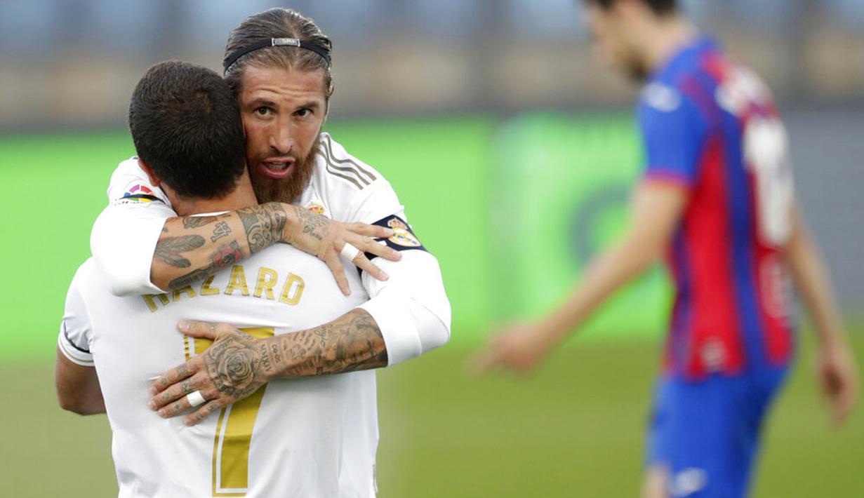 Bek Real Madrid, Sergio Ramos, melakukan selebrasi bersama Eden Hazard usai membobol gawang Eibar pada laga La Liga di Estadio Alfredo Di Stefano, Senin (15/6/2020). Real Madrid menang 3-1 atas Eibar. (AP/Bernat Armangue)