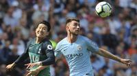 Bek Manchester City, Aymeric Laporte, berebut bola dengan pemain Tottenham Hotspur, Heung-Min Son, pada laga Premier League di Stadion Etihad, Sabtu (20/4). Manchester City menang 1-0 atas Tottenham Hotspur. (AP/Rui Vieira)