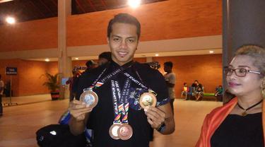 I Gede Siman Sudartawa memamerkan medali yang direbutnya di SEA Games 2017. (Liputan6.com/Dewi Divianta)