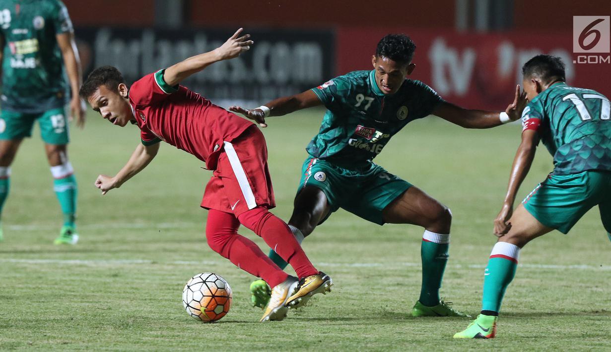 Pemain Timnas Indonesia U-19, Egy Maulana Fikri (kiri) mencoba lolos dari kawalan pemain PSS Sleman saat uji coba di Stadion Maguwohardjo, Sleman, Sabtu (12/8). Laga ini persiapan Timnas sebelum Piala AFF U-18, Myanmar. (Liputan6.com/Helmi Fithriansyah)