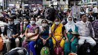 Orang India yang menunggu di stasiun kereta api memakai masker pelindung sebagai tindakan pencegahan terhadap pandemi Virus Corona. (Rajanish Kakade / AP Photo]