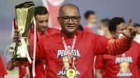 Pelatih Persija Jakarta, Sudirman, mengangkat trofi usai menjuarai Piala Menpora 2021 di Stadion Manahan, Solo, Minggu (25/4/2021). Persija mengalahkan Persib dengan agregat 4-1. (Bola.com/M Iqbal Ichsan)