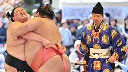 Pegulat sumo bertanding dalam turnamen Honozumo di Kuil Yasukuni, Tokyo, Jepang, 15 April 2019. Honozumo sudah digelar sejak seabad lalu. (TRIBALLEAU CHARLY/AFP)