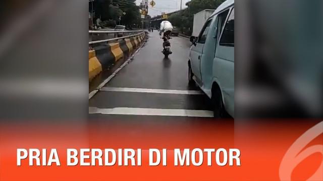 Ulah seorang pria ini tak patut dicontoh. Ketika mengendarai motor, ia tak mengenakan helm. Bukan hanya itu, pria itu juga nekat berdiri di atas motor.