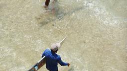 Dua wisatawan bersiap untuk bermain selancar di pantai Uluwatu Kuta Selatan di Kabupaten Badung, Bali pada 20 Desember 2018. Jutaan turis mancanegara datang ke Bali untuk berburu spot berselancar paling menantang. (Photo by SONNY TUMBELAKA / AFP)