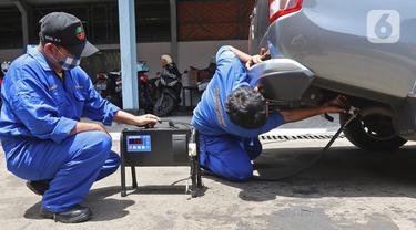 Petugas melakukan uji emisi buang kepada kendaraan di Kantor Dinas Lingkungan Hidup DKI Jakarta kawasan Kramat Jati, Jakarta, Selasa (3/11/2020). Uji emisi yang diberlakukan secara gratis itu akan rutin digelar setiap Selasa dan Kamis. (Liputan6.com/Herman Zakharia)