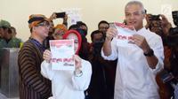 Calon Gubernur Jawa Tengah nomor urut 1, Ganjar Pranowo bersama istri, Siti Atiqoh menunjukkan surat suara pada pelaksanaan Pilkada Serentak 2018 di Tempat Pemungutan Suara ( TPS) 02 Kelurahan Gajahmungkur Kota Semarang, Rabu (27/6). (Liputan6.com/Gholib)