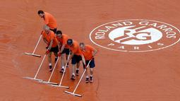 Pekerja stadion mengepel untuk membuang air hujan saat pertandingan perempat final Perancis Terbuka di stadion Roland Garros, Paris (6/6). (AP/Alessandra Tarantino)