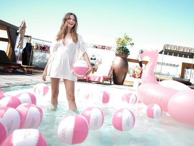 Model cantik , Behati Prinsloo tertawa di atas kolam renang saat menghadiri peluncuran pakaian renang Victoria Secret di Beverly Hills, California, USA (8/3). Behati merupakan istri dari vokalis Maroon 5, Adam Levine. (Jason Kempin/Getty Images/AFP)