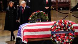 Presiden AS, Donald Trump dan Melania Trump saat akan memberikan penghormatan terakhir kepada George HW Bush di Gedung Capitol, Washington, Senin (3/12). Bush senior meninggal pada Jumat, 30 November 2018, di usia 94. (Pablo MARTINEZ MONSIVAIS/POOL/AFP)