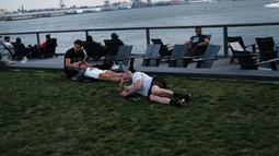Orang-orang beristirahat saat menikmati musim semi yang hangat di tepi air di Manhattan di New York City (8/4). Sebagian besar Pantai Timur mengharapkan suhu hangat terus sepanjang minggu. (Spencer Platt/Getty Images/AFP)