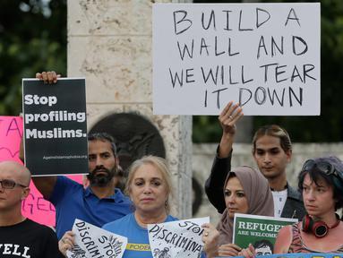 Pengunjuk rasa berdemontrasi di pusat kota Miami, AS, Kamis (26/1). Pengunjuk rasa menolak kebijakan Presiden AS, Donald Trump yang membatasi warga Muslim masuk ke AS. (AP Photo / Alan Diaz)