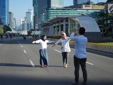 Dua orang wanita berfoto dengan latar belakang Jalan MH Thamrin yang masih ditutup oleh aparat keamanan di Jakarta, Jumat (24/5/2019). Ditutupnya Jalan MH Thamrin terkait unjuk rasa menolak hasil Pemilu 2019 dimanfaatkan sebagian warga untuk berfoto. (Liputan6.com/Immanuel Antonius)