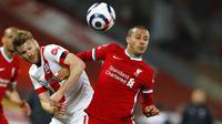 Penyerang Liverpool, Thiago Alcantara, duel udara dengan pemain Southampton, Nathan Redmond, pada laga Liga Inggris di Stadion Anfield, Minggu (9/5/2021). Liverpool menang dengan skor 2-0. (Phil Noble/Pool via AP)