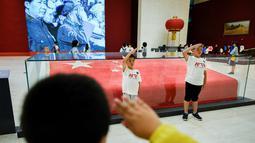 Anak-anak memberi hormat ketika mereka berpose di depan bendera nasional Tiongkok yang dikibarkan pada 1 Oktober 1949 di Museum Nasional China di Beijing (22/8/2019). Tujuan museum ini adalah untuk edukasi mengenai seni dan sejarah Tiongkok. (AFP Photo/Wang Zhao)