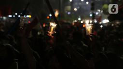 Peserta aksi unjuk rasa memegang lilin saat doa bersama lintas agama di Kawasan Patung Kuda, Jakarta, Selasa (10/11/2020). Sejumlah massa gabungan dari berbagai organisasi buruh dan mahasiswa berunjuk rasa menolak pengesahan Omnibus Law UU Cipta Kerja. (Liputan6.com/Helmi Fithriansyah)