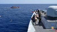 Angkatan Laut (AL) Italia merilis gambar ketika perahu yang berisi para migran terbalik di lepas pantai Libya, Rabu (25/5). Tujuh orang tewas tenggelam, sementara 500 orang lainnya berhasil diselamatkan dalam insiden tersebut (STR/AFP MARINA MILITARE/AFP)
