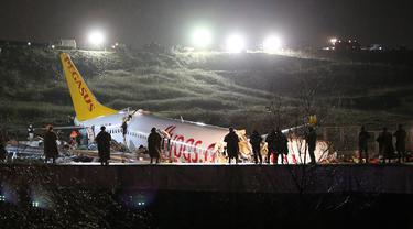 Tim penyelamat dan petugas pemadam kebakaran bekerja setelah sebuah pesawat tergelincir di landasan pacu Bandara Sabiha Gokcen, Istanbul, Turki, Rabu (5/2/2020). Pesawat milik maskapai Pegasus Airlines tersebut keluar dari landasan pacu dan terbelah menjadi tiga bagian. (AP Photo/Emrah Gurel)