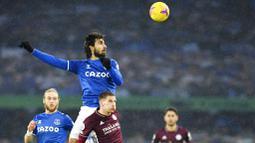 Pemain Everton, Andre Gomes duel udara dengan pemain Leicester City, Marc Albrighton, pada laga Liga Inggris di Stadion Goodison Park, Rabu (27/1/2021). Kedua tim bermain imbang 1-1. (Paul Ellis/Pool via AP)