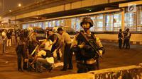 Sejumlah polisi berjaga di sekitar Terminal Kampung Melayu, Jakarta, Rabu (24/5). Polisi dari Polres Jakarta Timur dan Gegana Polda Metro Jaya tengah menyusuri lokasi ledakan. (Liputan6.com/Angga Yuniar)
