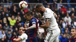 Striker Real Madrid, Karim Benzema, mencetak gol ke gawang Eibar pada laga La Liga di Stadion Santiago Bernabeu, Sabtu (6/4). Real Madrid menang 2-1 atas Eibar. (AFP/Gabriel Bouys)