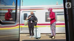 Petugas memberikan salam kepada penumpang yang akan menaiki KA Taksaka di Stasiun Gambir, Jakarta, Sabtu (4/8/2021). Dalam rangka memperingati hari pelanggan nasional, PT KAI Daop 1 Jakarta membagikan ratusan bingkisan kepada penumpang kereta api. (Liputan6.com/Faizal Fanani)