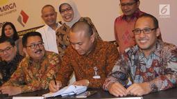Dirut Jasa Marga Desi Arryani menyaksikan Pemimpin Divisi Korporasi & Komersial Bank BJB Dicky Syahbandinata menandatangani perjanjian kredit sindikasi Jasa Marga terkait pembangunan ruas Tol Cikampek II, Jakarta, Selasa (31/7). (Merdeka.com/Arie Basuki)