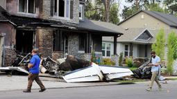 Pejabat Federal Aviation Administration menyelidiki lokasi pesawat yang sengaja menabrak rumah di Payson, Utah, AS, Senin (13/8). Istri dan putra sang putra yang berada di dalam rumah dapat menyelamatkan diri. (Scott G Winterton/The Deseret News via AP)