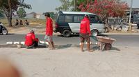 Pemuda di Kecamatan Arosbaya bergotong royong menambal jalan berlubang. (Liputan6/Musthofa Aldo)