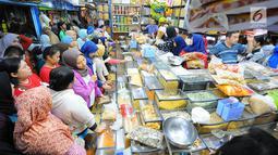 Sejumlah pembeli mengantre saat membeli kue kering di Pasar Jatinegara, Jakarta, Senin (27/5/2019). Jelang Idul Fitri 2019, banyak warga berburu makanan ringan seperti kue kering untuk jamuan di hari raya. (Liputan6.com/Angga Yuniar)