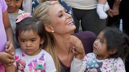 Paris Hilton tersenyum saat memeluk dua anak selama selama kunjungan bertemu tujuh keluarga yang terkena dampak gempa pada September 2017 di San Gregorio Atlapulco, Meksiko (12/11). (AFP Photo/Antonio Nava)