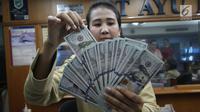 Teller tengah menghitung mata uang dolar di penukaran uang di Jakarta, Junat (23/11). Nilai tukar dolar AS terpantau terus melemah terhadap rupiah hingga ke level Rp 14.504. (Liputan6.com/Angga Yuniar)