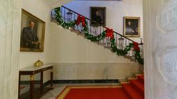 Dekorasi Natal menghiasi tangga utama atau Grand Staircase di Gedung Putih, Washington DC, Senin (26/11). Gedung Putih telah resmi didekorasi untuk menyambut Natal 2018 dengan mengangkat tema 'American Treasures'. (AP/Carolyn Kaster)