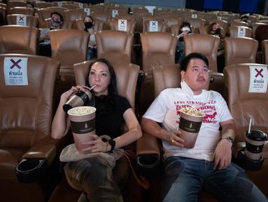 Pengunjung minum minuman ringan ketika mereka berlatih menjaga jarak sosial selama film di bioskop Paragon Cineplex di Bangkok, Thailand, Senin (1/6/2020). Mulai 1 Juni, pihak berwenang Thailand mengizinkan bioskop dan bisnis lain untuk dibuka kembali. (AP Photo/Sakchai Lalit)