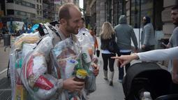 Seorang warga menanyakan kantung-kantung plastik berisi sampah-sampah pada tubuh Rob Greenfield di New York, AS, 4 September 2016. Aktivis lingkungan itu bertekad untuk memakai semua sampah yang ia hasilkan selama 30 hari. (AFP Photo/Bryan R. Smith)