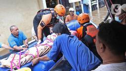 Relawan dan keluarga menaikkan jenazah warga lansia ke atas perahu karet saat banjir di Cipinang Melayu, Jakarta Timur, Jumat (19/2/2021). Seorang nenek (80) meninggal di kediamannya, di lokasi banjir, di RW 04, kawasan tersebut karena sakit dan sudah lanjut usia. (Liputan6.com/Herman Zakharia)