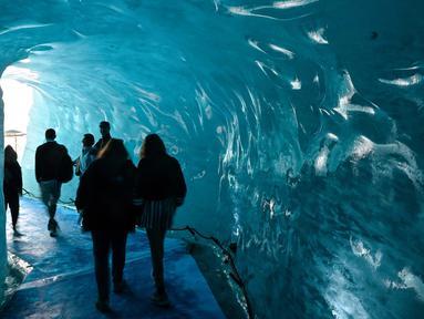 "Wisatawan mengunjungi sebuah gua es yang dikenal dengan ""La Grotte de Glace"", di gletser Mer de Glace (Lautan Es) di Chamonix-Mont-Blanc, Pegunungan Alpen Prancis, Jumat (19/7/2019). Gua yang berada di lereng Mont Blanc ini memiliki panjang 7 km dengan kedalaman 200 meter. (PHILIPPE DESMAZES/AFP)"